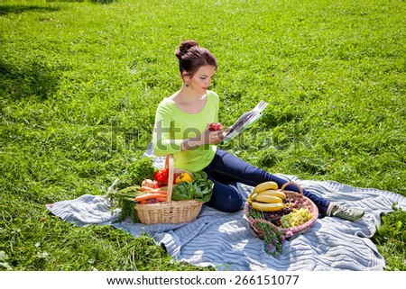 Young girl with a basket of vegetables and fruits at picnic outdoors, healthy food concept - stock photo