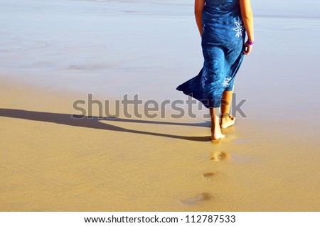 Young girl with a blue dress walking barefoot in the beach - stock photo