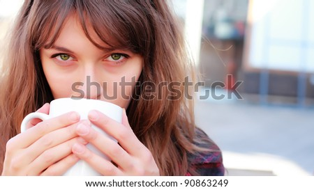 young girl with a cup of coffee. Focus on the eyes. - stock photo