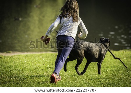 Young girl with a dog playing on the grass by the lake - stock photo