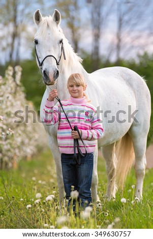 Young girl with a horse in blooming garden. - stock photo