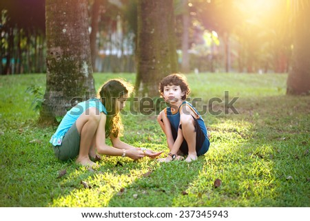 Young girl with a little brother playing in the garden during at sun down. Concept of happy sibling. - stock photo