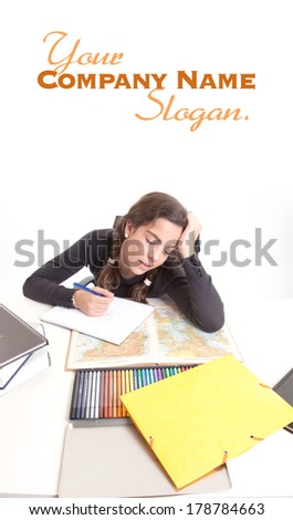 Young girl with a tired expression doing schoolwork  - stock photo