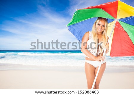 young girl with a white bikini walking with a sunshade along a beautiful beach with a turquoise sea - stock photo