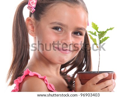 Young girl with an oak sapling - stock photo