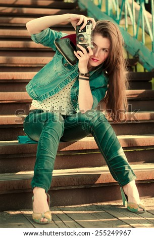 Young girl with an old camera on the street in the spring.Vintage style, toning. - stock photo