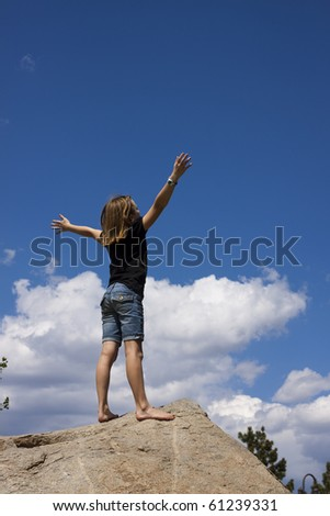 young girl with arms raised in worship - stock photo