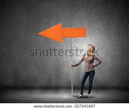Young girl with arrow signboard in empty room - stock photo