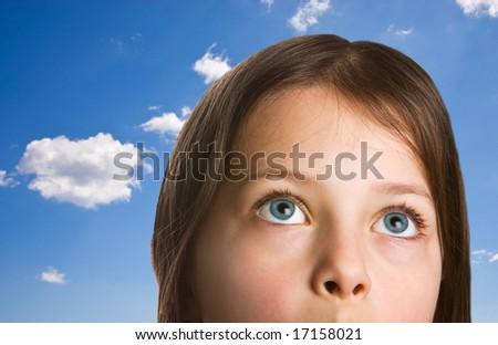 Young Girl with Big Blue Eyes against a Sky Background - stock photo