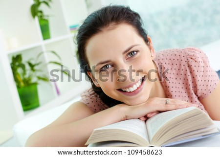 Young girl with book looking at camera and smiling - stock photo