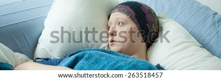 Young girl with cancer in hospital bed - stock photo