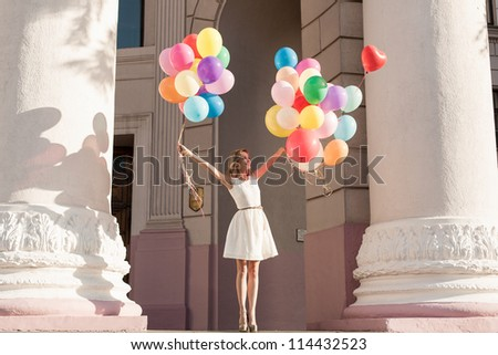 Young girl with colorful latex balloons keeping her dress, urban scene, outdoors - stock photo