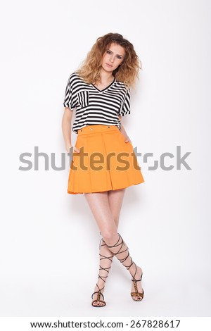 young girl with curly hair wearing orange skirt and marine tshirt with stripes on white background - stock photo