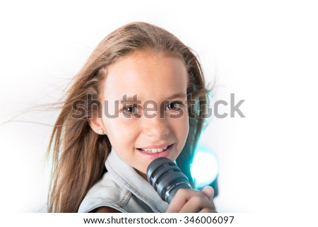 Young girl with denim jacket singing while holding a microphone on a white background - stock photo