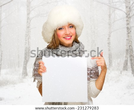 Young girl with empty poster at snowy winter forest - stock photo