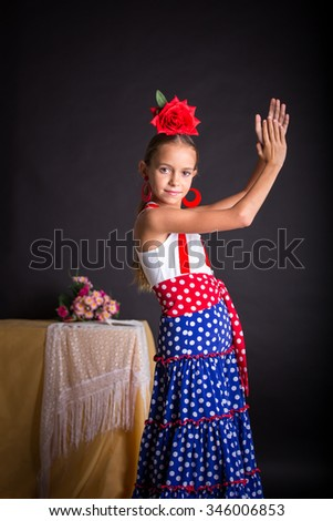 Young girl with flamenco outfit clapping hands on black background - stock photo