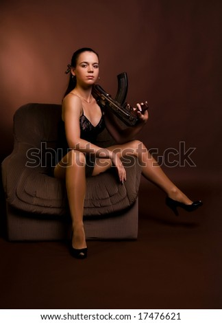 Young girl with gun, on brown - stock photo