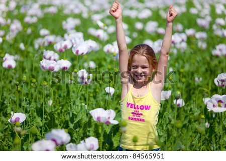 Young girl with hands up in field of white poppy - stock photo