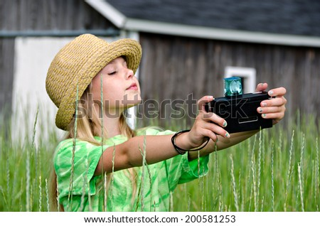 young girl with hat taking a selfie with an old-fashioned camera - stock photo