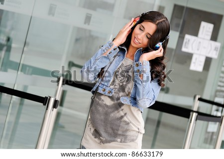 Young girl with headphones listening to the music and dancing in the street - stock photo