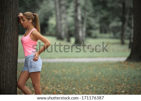 Young girl with headphones near tree - stock photo
