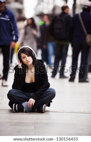 Young girl with headphones sitting on sidewalk - stock photo