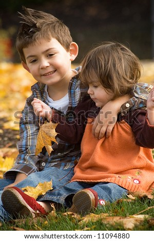 Young girl with her brother in an orange sweater and jeans playing in the fall leaves - stock photo