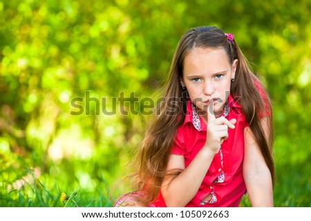 Young girl with her finger over her mouth, hushing. - stock photo