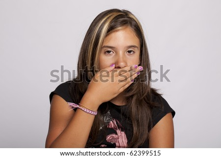 young girl with her hand over mouth - stock photo