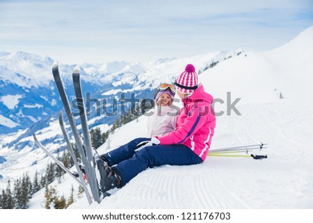 Young girl with her mother in a ski outfit sitting on the snowy hill in the Zillertal Arena, Austria - stock photo