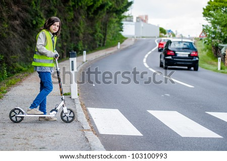 Young girl with her scooter will go on the crosswalk - stock photo