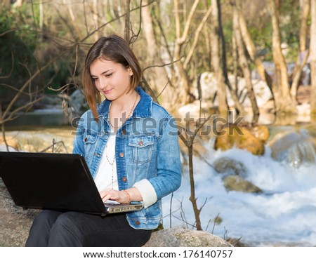 Young girl with laptop on rock near waterfall - stock photo
