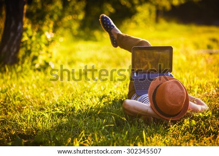 young girl with laptop outdoors  - stock photo
