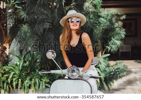young girl with long hair in sunglasses in a black t-shirt tattoo on his shoulder in white pants with red lipstick posing on a retro scooter Vespa colors taifani vintage style straw hat with a stylish - stock photo