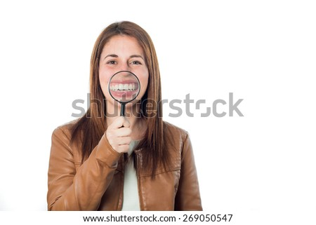 young girl with magnifying glass in her eye and smiling isolated on white background - stock photo