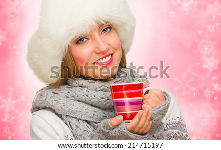 Young girl with mug on red winter background - stock photo