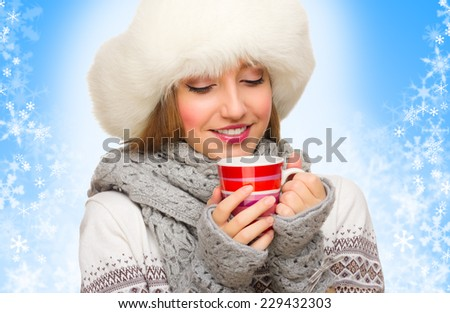 Young girl with mug on winter background - stock photo