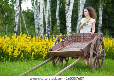 Young girl with old wooden cart on the field with green grass and yellow flowers - stock photo