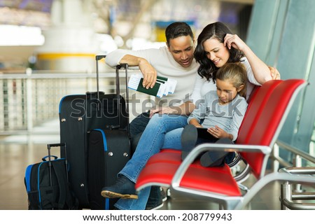 young girl with parents using tablet computer at airport while waiting for their flight - stock photo