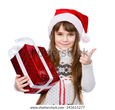 young girl with red santa hat holding gift box and showing thumbs up. isolated on white background - stock photo