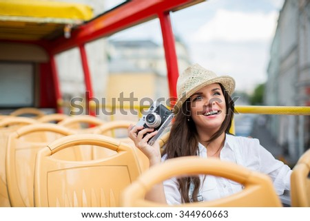Young girl with retro camera in the tour bus - stock photo