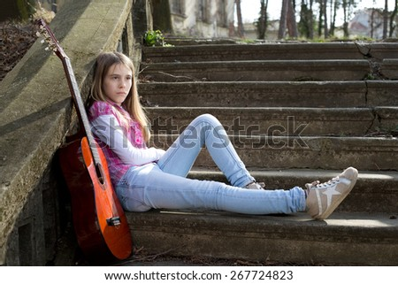 Young Girl With Sad Expression on Her Face Leaning Against the Wall and Looking Worried - stock photo
