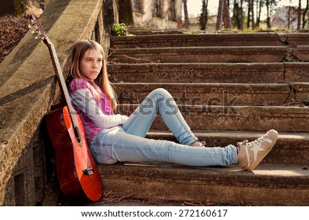 Young Girl With Sad Expression on Her Face Leaning on the Wall on Sunny Spring Day  - stock photo