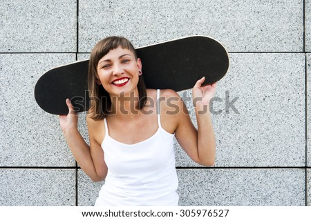 Young girl with skateboard on her shoulders in the city by the wall smiling. - stock photo