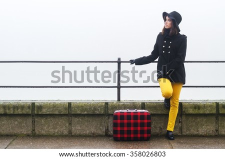 Young girl with suitcase traveling somewhere on cold misty autumn day. - stock photo