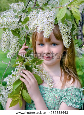 Young girl with the blossoming bird cherry branches - stock photo