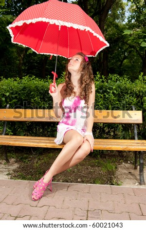 Young girl with umbrella sitting on bench - stock photo