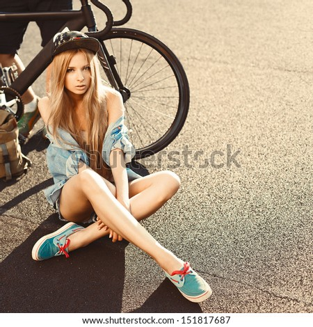 Young girl with young man win fixed gear bike posing outdoor on the ground. Cute blonde sport fashion summer portrait - stock photo