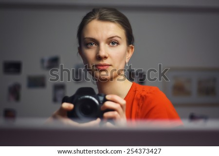 Young girl woman holding a digital camera taking picture of herself looking into the mirror - stock photo