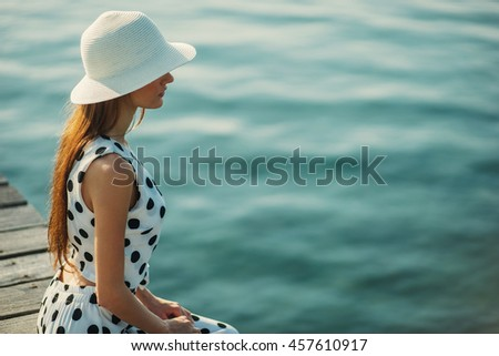 Young girl woman in white hat and retro dotted dress sitting at wooden pier and looking on the sea sunset sunrise. Summer background. Copy space. Travel inspiration. Postcard concept. Vintage effect.  - stock photo